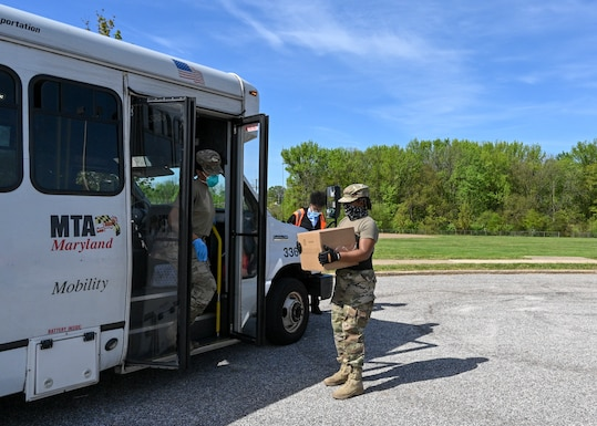 Members of the Maryland Air National Guard place boxes of groceries on a Maryland Transportation Mobility bus for a member of the community while supporting efforts by the Maryland Food Bank and Baltimore County Department of Parks and Recreation to distribute meals and groceries at the Mars Estates Police Athletic League center in Essex, Md., May 2, 2020. The mission helps food insecure citizens have enough while schools and work places are closed. (U.S. Air National Guard photo by Tech. Sgt. Enjoli Saunders)