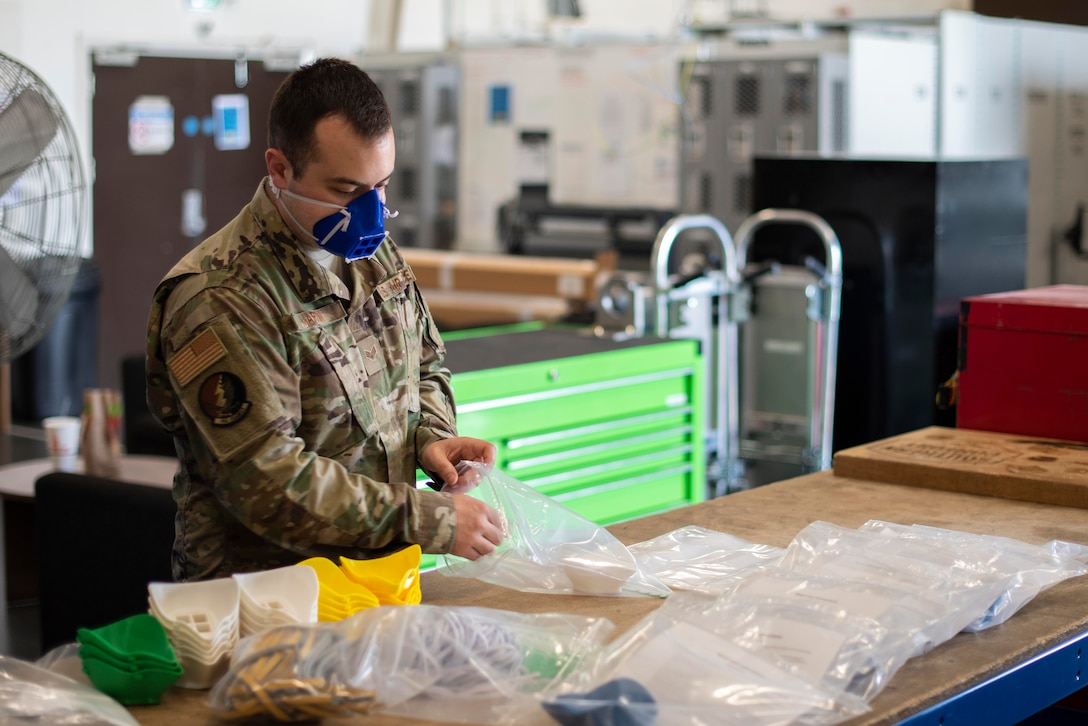 U.S. Air Force Senior Airman Carl Martin, support technician assigned to the 352d Special Operations Aircraft Maintenance Squadron, 352d Special Operations Wing, creates mask kits, April 27, 2020, at RAF Mildenhall, England. Designed to protect wearers from COVID-19, the masks must be assembled after they are printed, a process that involves using warm water to shape the mask to the face. The 352d Special Operations Wing is the sole Air Force special operations unit in the European Theater. (U.S. Air Force photo by Airman 1st Class Joseph Barron)