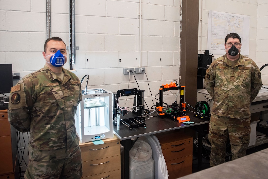 From left to right, U.S. Air Force's Senior Airman Carl Martin, 352d Special Operations Aircraft Maintenance Squadron support technician, and Staff Sgt. Alex Bruce, 352d SOAMXS MC-130J equipment custodian, stand in front of the 3D printers they use to construct plastic masks, April 27, 2020, at RAF Mildenhall, England. Bruce and Martin have produced more than 100 masks for squadron members in the past month, following DoD health guidelines on the use of cloth face coverings by using 3D printers to engineer face masks in an effort to combat the spread of Coronavirus. The 352d Special Operations Wing is the sole Air Force special operations unit in the European Theater. (U.S. Air Force photo by Airman 1st Class Joseph Barron)