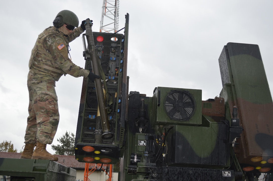 A soldier loads a missile into a short-range air defense missile system.