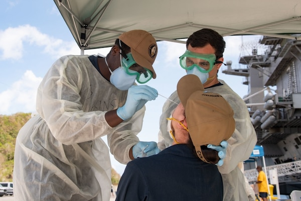 Two male Naval hospital workers swab a female sailor.