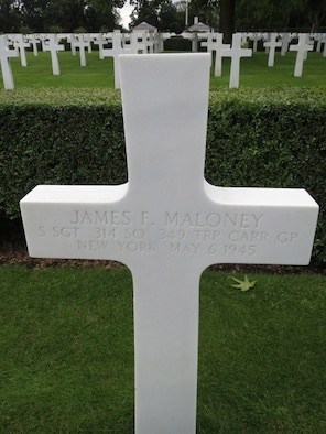 A marble white cross signifies the final resting place of Staff Sgt. James F. Maloney in England.
