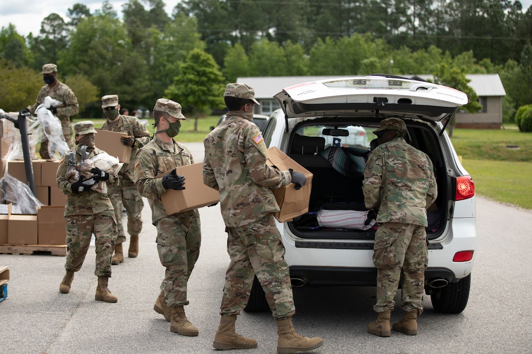 Soldiers loading boxes of food into a vehicle.