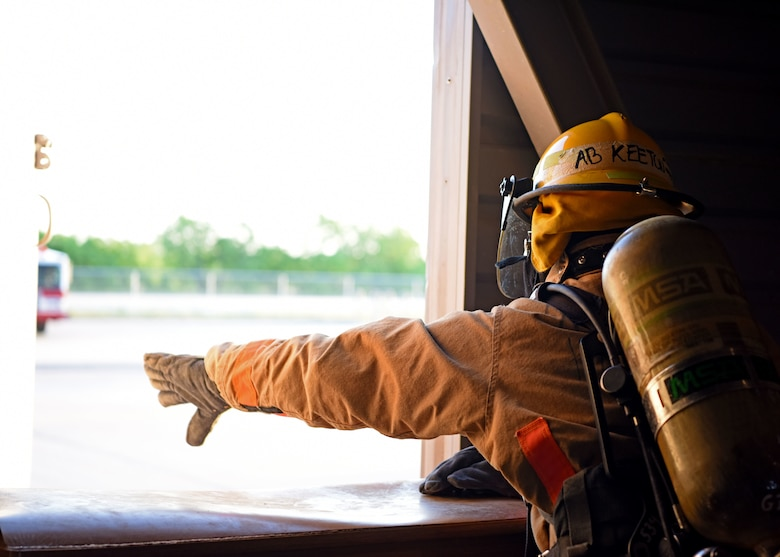 A 312th Training Squadron student pushes open a window to ventilate a building at the Louis F. Garland Department of Defense Fire Academy on Goodfellow Air Force Base, Texas, May 7, 2020. The rescue team was fitted with blindfolds to simulate smoke, they were then sent in to ventilate the building to dissipate the simulated smoke. (U.S. Air Force photo by Airman 1st Class Ethan Sherwood)