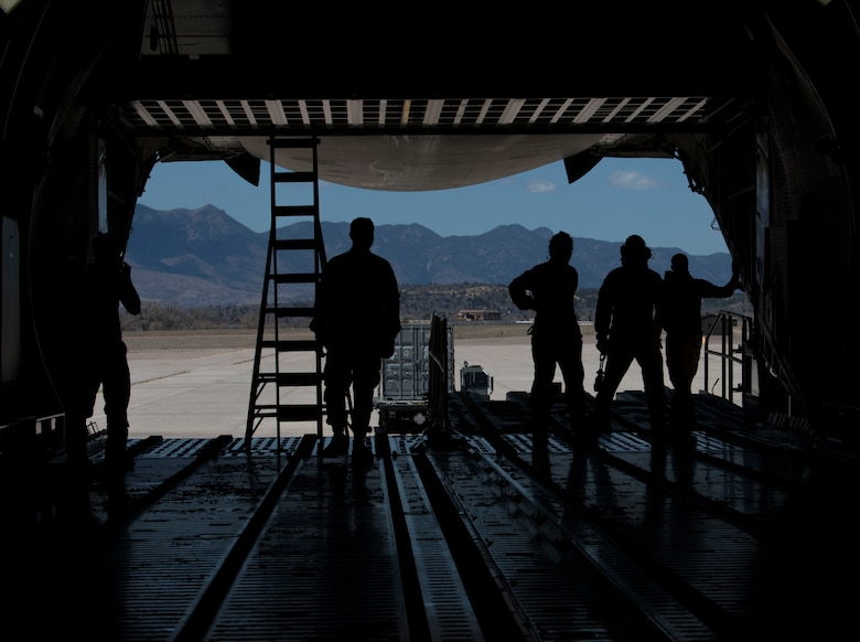 Airmen from the 21st Logistics Readiness Squadron, the 22nd Airlift Squadron watch as a K Loader is directed after putting cargo pallets onto a C-5M Super Galaxy, April 27, 2020 on Peterson Air Force Base, Colorado. The 21st LRS loaded the cargo to assist in a Space and Missile Systems Center mission to bring supplies to warfighters down range. The 21st LRS was able to coordinate with the SMC, receive the cargo, inspect it and have it on a plane in less than two weeks. This fast turnaround was to match the speed of the SMC Rapid Reaction Branch needed the cargo to be sent downrange. (U.S. Air Force photo by Airman 1st Class Andrew J. Bertain)