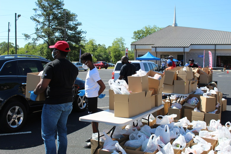 Photo shows individuals with boxes of food and handing them to families in cars as they drive by.