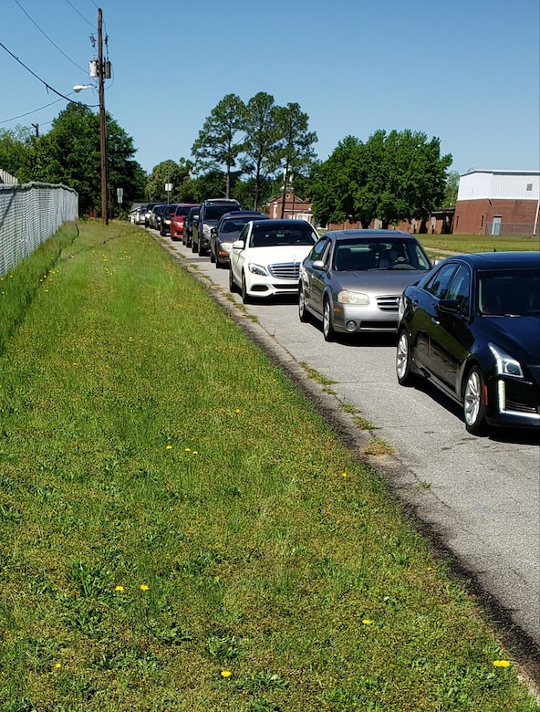 Photo shows cars lined up next to a ball park.
