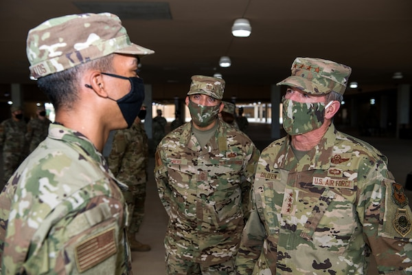 Air Force Chief of Staff Gen. David L. Goldfein (right) and Chief Master Sgt. Manny Pineiro (center), the service's first sergeant special duty manager, talks with an Airman after basic military training graduation May 7, 2020, at Joint San Antonio-Lackland, Texas.