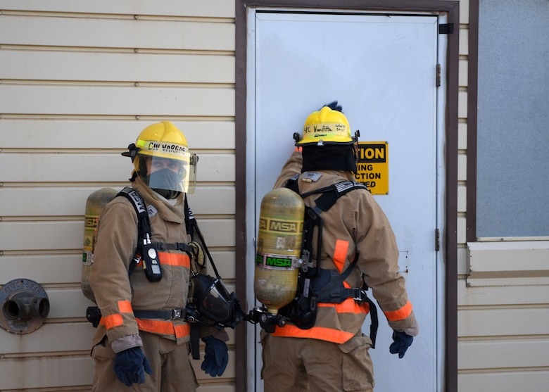 The 312th Training Squadron students feel a door for heat before entering a building at the Louis F. Garland Department of Defense Fire Academy on Goodfellow Air Force Base, Texas, May 6, 2020. Students were tested on what they knew and how well they accomplished set tasks. (U.S. Air Force photo by Airman 1st Class Ethan Sherwood)