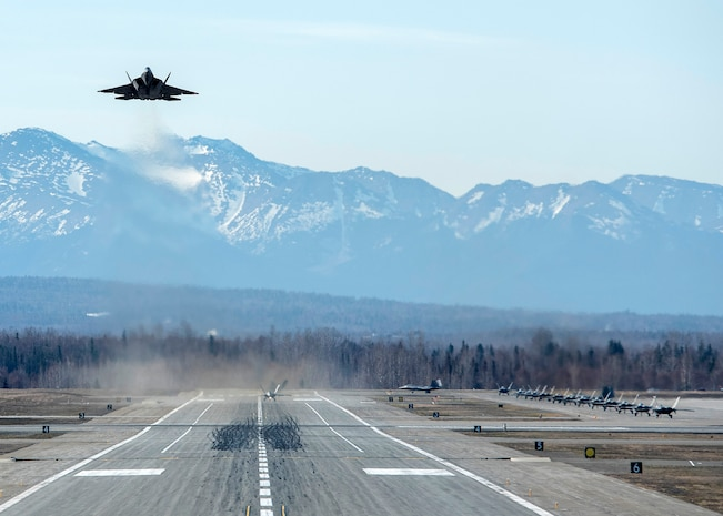 A U.S. Air Force F-22 Raptor takes off while other Raptors taxi to the runway following a close formation taxi known as an elephant walk, at Joint Base Elmendorf-Richardson, Alaska, May 5, 2020. This event displayed the ability of the 3rd Wing, 176th Wing and the 477th Fighter Group to maintain constant readiness throughout COVID-19 by Total Force Integration between active-duty, Guard and Reserve units to continue defending the U.S. homeland and ensuring a free and open Indo-Pacific.