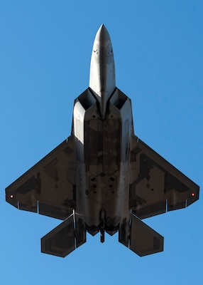 A U.S. Air Force F-22 Raptor flies over Joint Base Elmendorf-Richardson, Alaska, following a close formation taxi known as an elephant walk, May 5, 2020. This event displayed the ability of the 3rd Wing, 176th Wing and the 477th Fighter Group to maintain constant readiness throughout COVID-19 by Total Force Integration between active-duty, Guard and Reserve units to continue defending the U.S. homeland and ensuring a free and open Indo-Pacific.