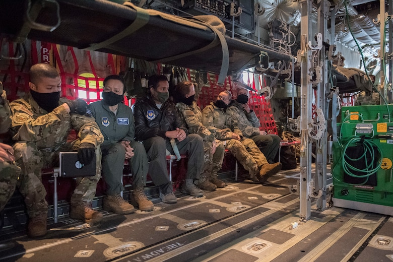 A row of Airmen sit aboard an aircraft.