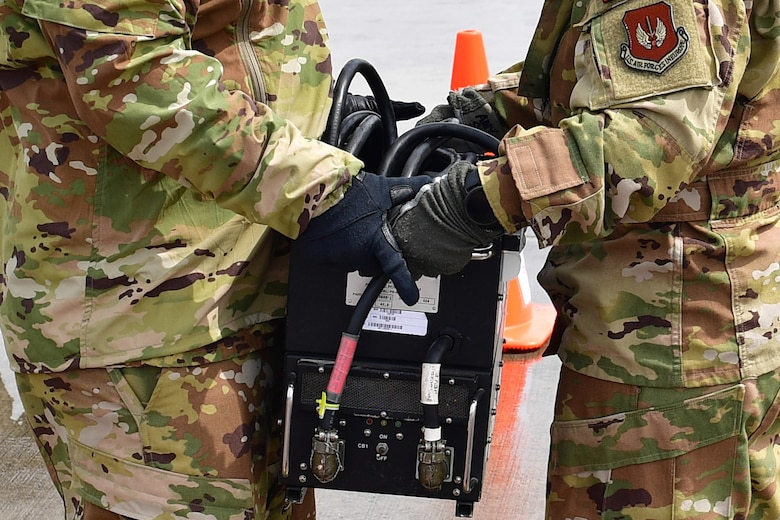 An Airman hands a portable power system to another Airman.