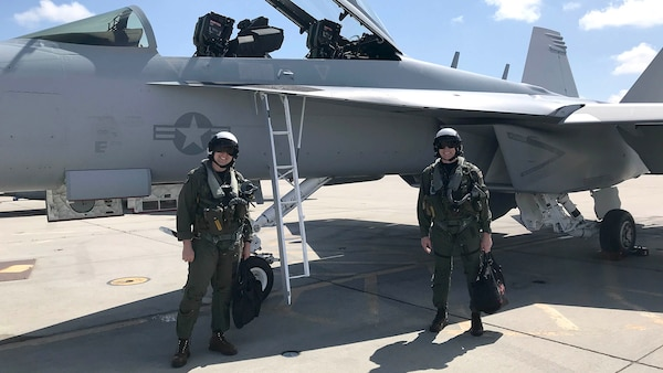 Two navy pilots pose near an aircraft.