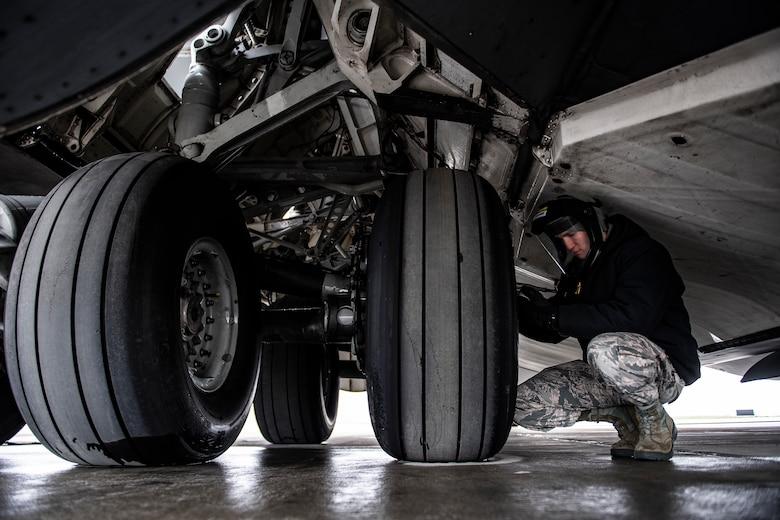 Senior Airman checks tire air pressure on a C-17
