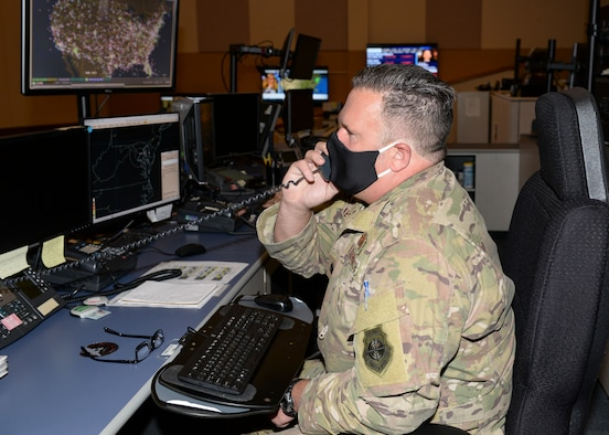 U.S. Air Force Lt. Col. G. Scott Key, senior offensive duty officer, 601st Air Operations Center (AOC), talks on the phone while practicing personal safety protocols due to the current COVID-19 global pandemic at Tyndall Air Force Base, Florida, May 4, 2020.