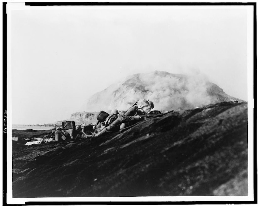 Marines lay prone with guns pointed on a black hill. A mountain rises in the background.
