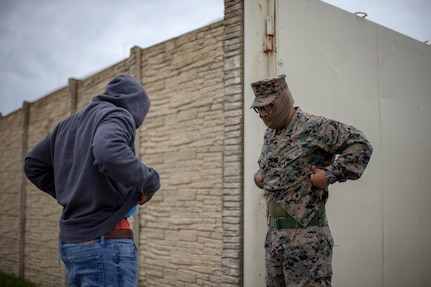 A U.S. Marine searches a role-player during a training event.