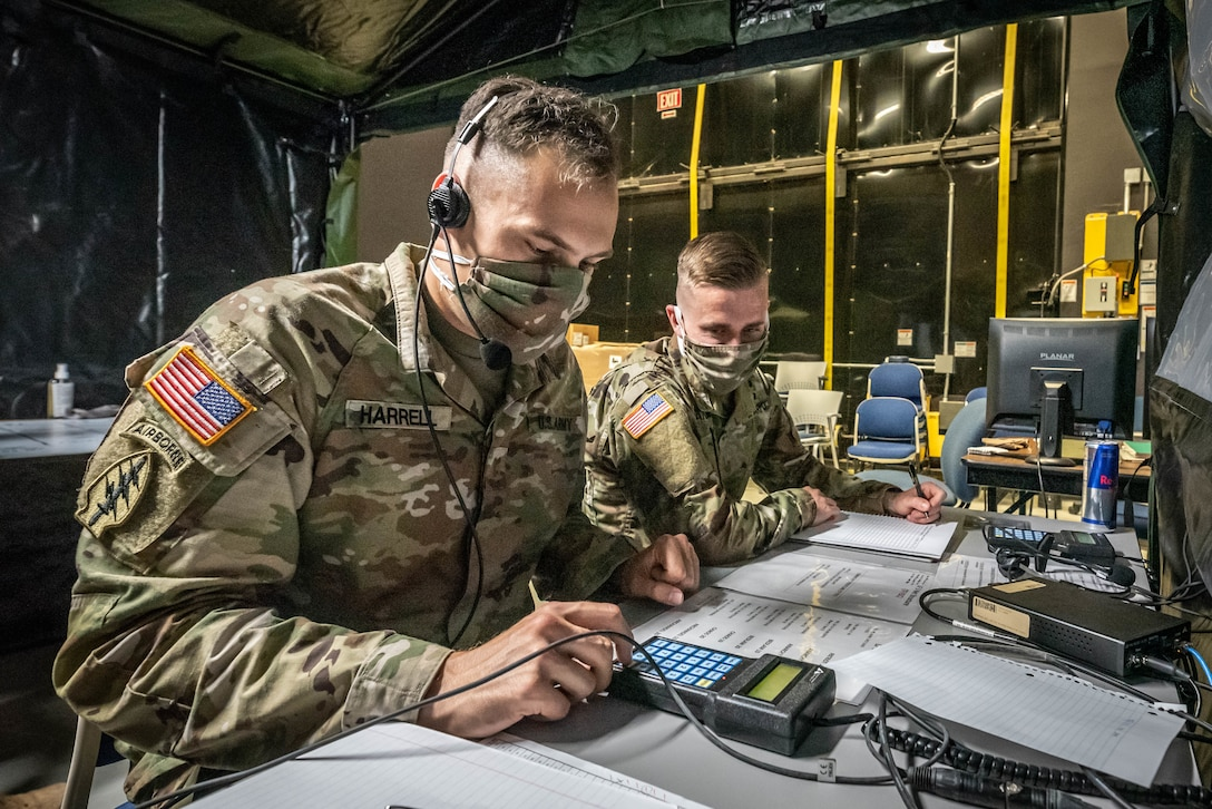 Masked soldiers do communications tasks.