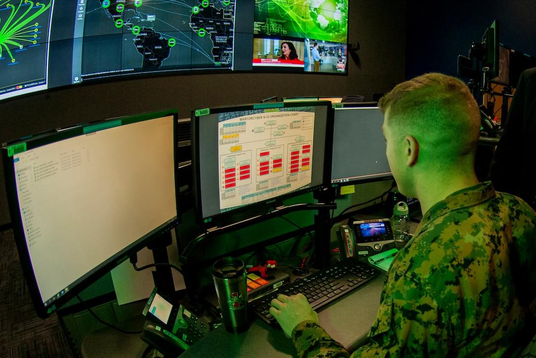 Marine operates computer.