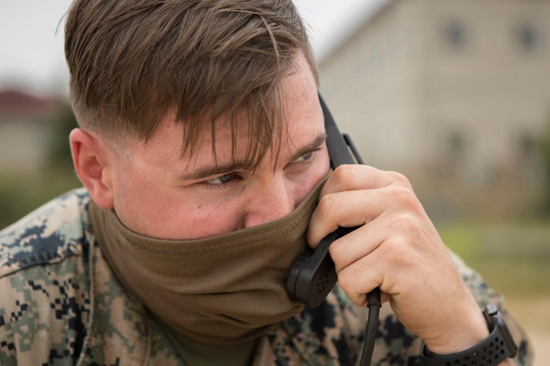 Radio operator with mask talks into radio.