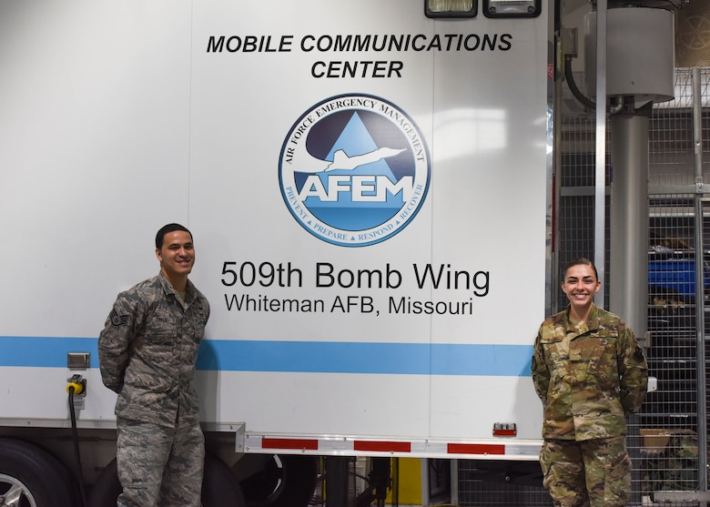 Staff Sergeant Kenneth Baker, assigned to the 509th Emergency Management Flight, assistant Non-commissioned Officer in charge of logistics, and Airman 1st Class Cassidy Knight, assigned to the Emergency Management Flight, plans and operations stand in front of the Emergency Management Mobile Communications Center, used during emergency situations in remote locations or in the event of damaged infrastructure.  Emergency management personnel operate out of the Emergency Operations Center when activated, to execute Installation Emergency Response Plan, which includes specific medical disease containment procedures and instructions.