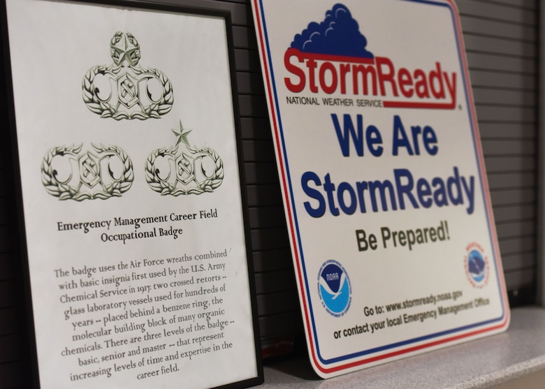 Signs in the 509th Bomb Wing Emergency Management work center display the Career Field Occupational Badge history and National Weather Service 'Storm Ready' information.  The badge symbols and adverse weather sign show the range of different Emergency Management responsibilities.
