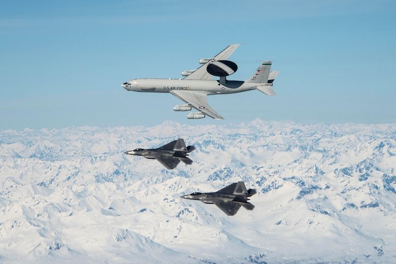An E-3 Sentry and two F-22 Raptors assigned to Joint Base Elmendorf-Richardson (JBER) in Anchorage, Alaska fly over mountains in Alaska May 5, 2020.