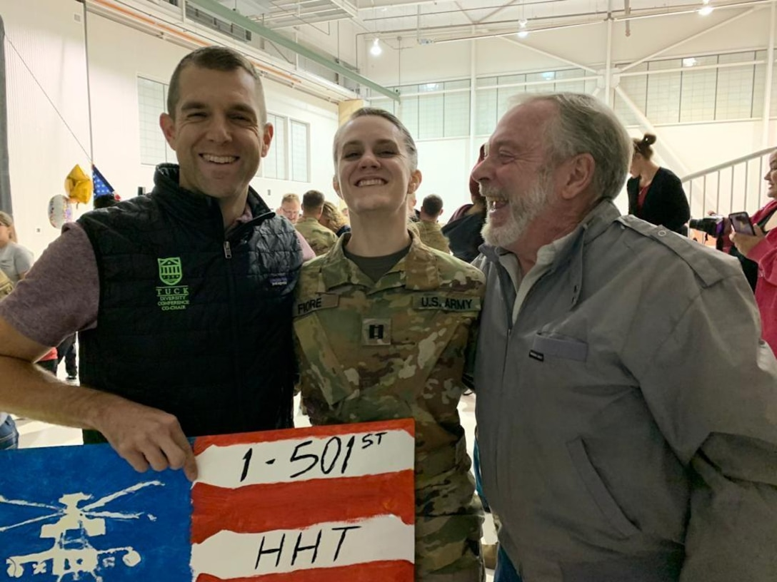 A soldier stands smiling with her father and grandfather on either side of her.