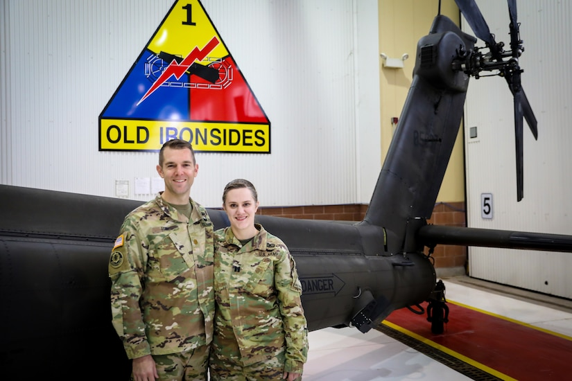 Two soldiers pose in front of the tail end of a helicopter.