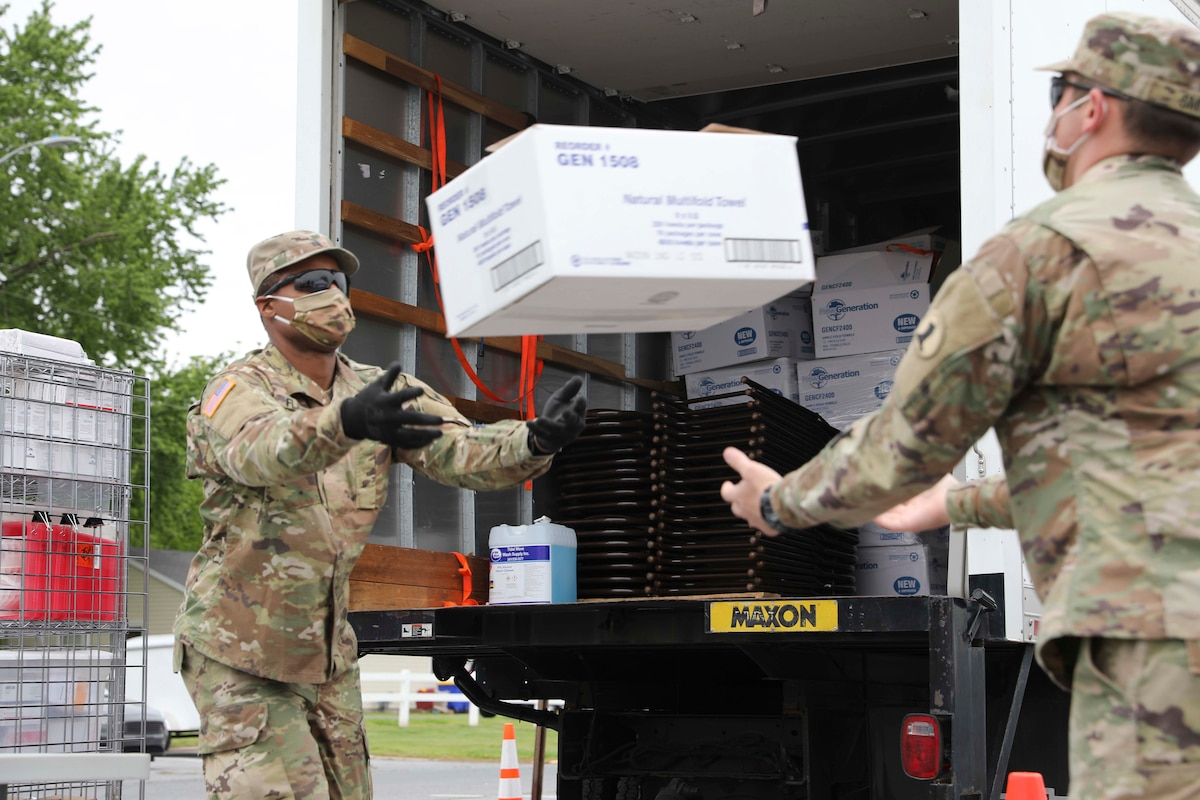 Two soldiers wearing face masks offload boxes from a truck.