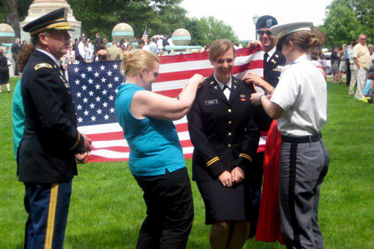 A soldier stands smiling around her family as they affix decorations to her uniform.