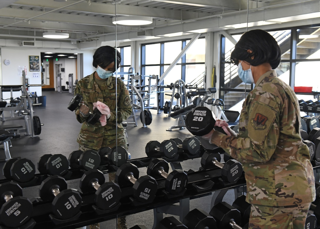 U.S. Air Force Tech. Sgt. Sharniece Clary, 9th Force Support Squadron fitness center program manager, sanitizes dumbbells in the Harris Fitness Center at Beale Air Force Base, California, May 6, 2020. The fitness center personnel disinfected every piece of equipment found in the facility while following Centers of Disease Control guidelines, and using standard Environmental Protection Agency approved disinfectants. (U.S. Air Force photo by Airman 1st Class Luis A. Ruiz-Vazquez)