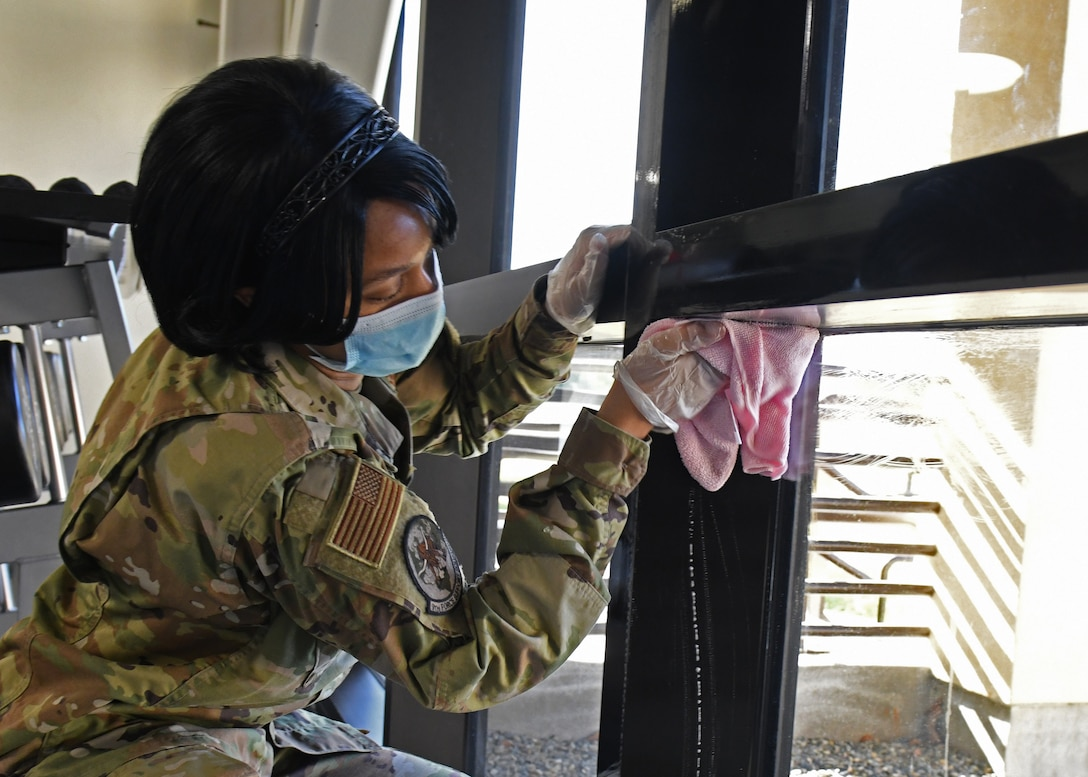 U.S. Air Force Tech. Sgt. Sharniece Clary, 9th Force Support Squadron fitness center program manager, disinfects a window frame in the Harris Fitness Center at Beale Air Force Base, California, May 6, 2020. A deep cleansing of the facility was conducted to ensure the safety and health of the base community from COVID-19. (U.S. Air Force photo by Airman 1st Class Luis A. Ruiz-Vazquez)