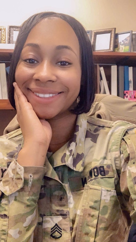 Black female in green camouflage uniform.