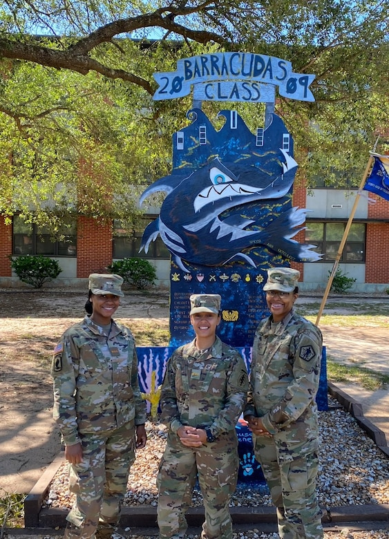 Three females in green camouflage uniforms stand a blue sign outside of a building.