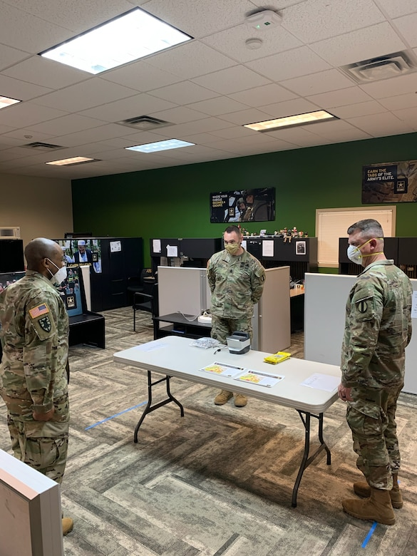 Three males in green camouflage uniforms and face masks stand around a table in a room with green and grey walls and grey chevron carpets.