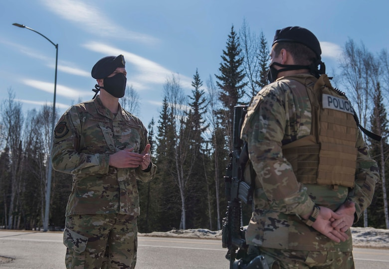 U.S. Air Force Tech. Sgt. Matthew R. Dobbins, the 354th Security Forces Squadron (SFS) non-commissioned officer (NCO) in charge of operations, performs a post briefing with Senior Airman Justin Wilson, a 354th SFS response force officer, at Eielson Air Force Base, Alaska, April 28, 2020.