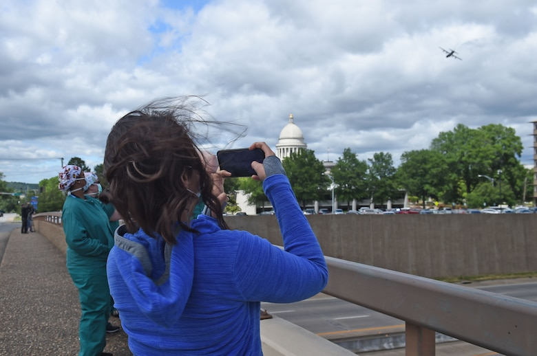 Spectators watch as two C-130s fly over the city