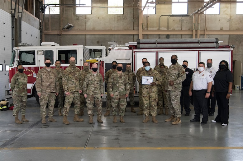 Col. Lee Gentile, 47th Flying Training Wing commander, and Chief Master Sgt. Robert L. Zackery III, 47th Command Chief, present Airman 1st Class Joquetta K. Rolle, a 47th Civil Engineer Squadron firefighter, with her Senior Airman Below-the-Zone certificate on May 8, 2020, at Laughlin Air Force Base, Texas. Team members from the 47th Mission Support Group posed for photo with Rolle and congratulated her for the accomplishment. (U.S. Air Force photo by Senior Airman Marco A. Gomez)