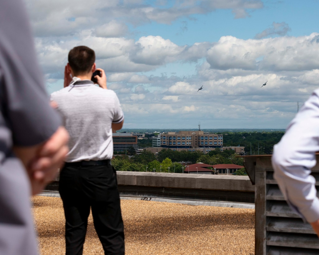 People watch as two C-130s fly over the city