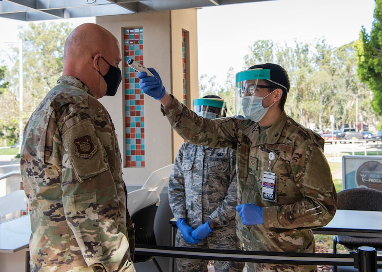 Senior Airman Avery Lake, 30th Medical Group mental health technician, checks the temperature of Gen. Jay Raymond, U.S. Space Force Chief of Space Operations and U.S. Space Command commander, before entering the 30th MDG for a tour, May 7, 2020, at Vandenberg Air Force Base, Calif. During the visit, Raymond observed and commended the members of Vandenberg AFB for their response to the COVID-19 global pandemic. (U.S. Air Force photo by Senior Airman Aubree Owens)