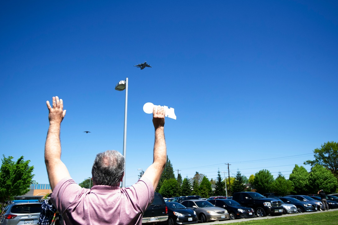 A Providence Regional Medical Center employee waves his hands at the two-ship C-17 Globemaster III formation May 8, 2020 in Everett, Washington. The 62nd Airlift Wing, based out of Joint Base Lewis-McChord, Wash., saluted American heroes who are on the frontline in the fight against COVID-19 with a morale flyover in the state's Puget Sound region. In January, Providence was the first U.S. hospital to report a COVID-19 case. (U.S. Air Force photo by Maj Candice Allen)