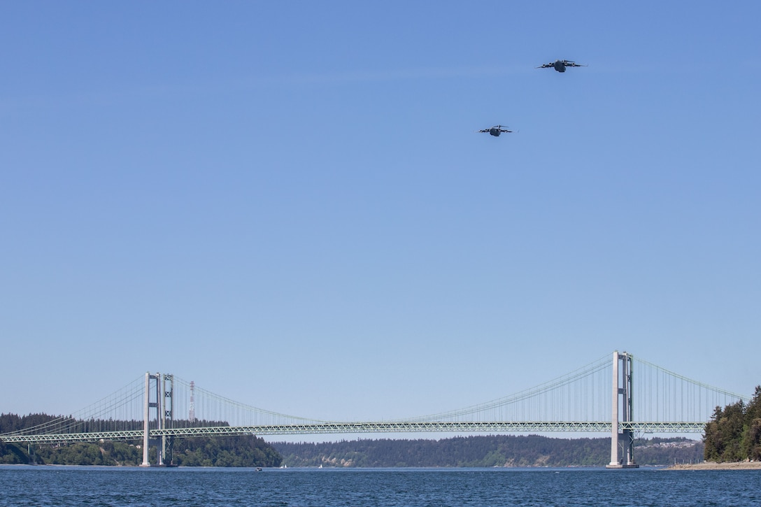 Two C-17 Globemaster IIIs assigned to the 62nd Airlift Wing conduct an Air Force Salutes morale flyover above the Tacoma Narrows Bridge in Tacoma, Wash., May 8, 2020. The flyover honored the American heroes at the forefront in the fight against COVID-19. (U.S. Air Force photo by Staff Sgt. Joshua Smoot)