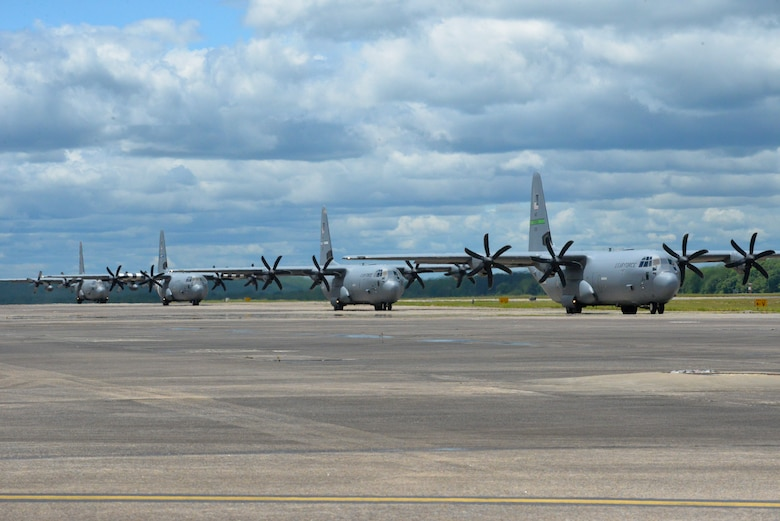 four C-130s taxi on the flight line