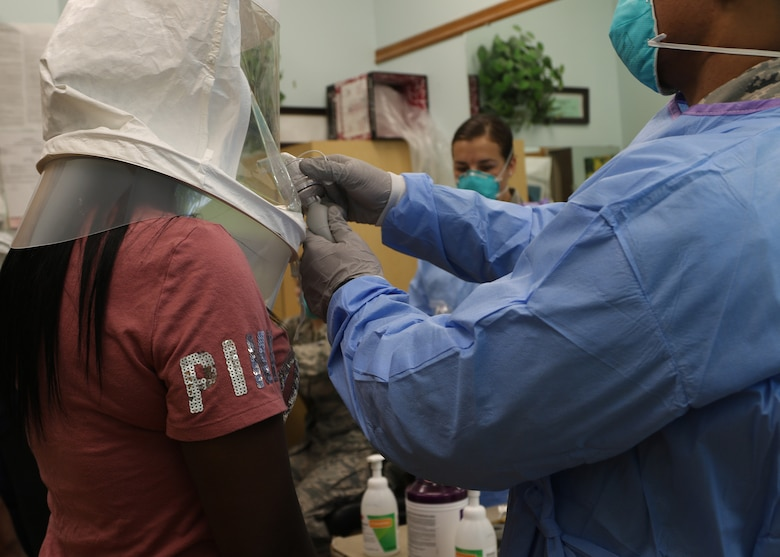 Airman 1st Class Traevonne Greene, 190th Air Refueling Wing, Kansas Air National Guard health service technician, sprays a non-toxic test solution into the hood of Latasha Benfer, medication aide for Homestead of Topeka, to test the N95 protective masks' ability to filter airborne particles during a fit test demonstration at Homestead of Topeka in Topeka, Kansas, May 6, 2020.