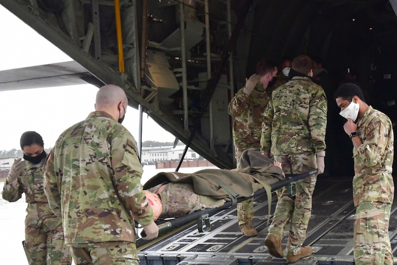 Airmen carry a mannequin on a gurney onto an aircraft.