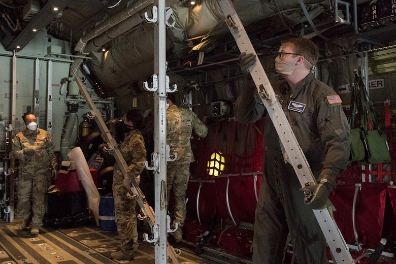Several Airmen break down and remove equipment inside an aircraft.