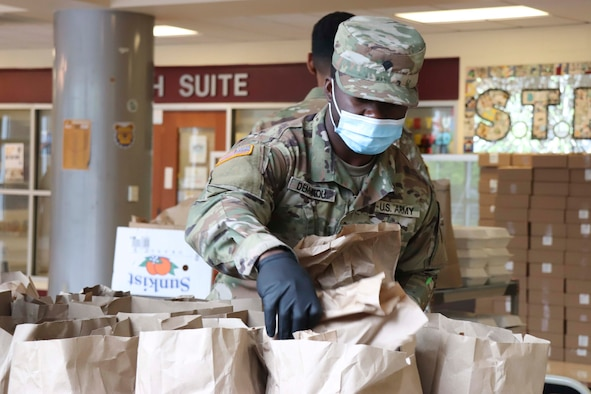A soldier wearing a face mask and gloves packs meals into paper bags.