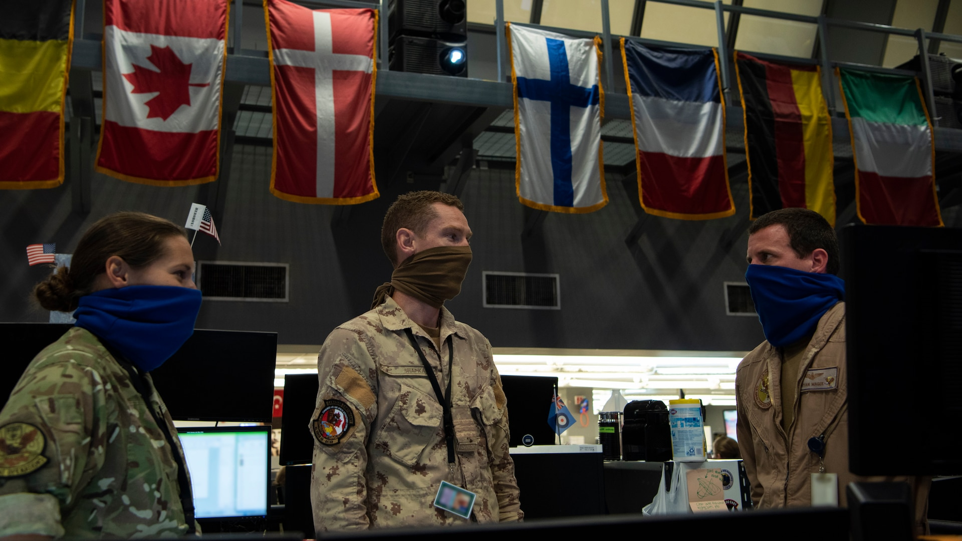 Coalition service members assigned to the Combined Air Operations Center discuss operations at Al Udeid Air Base, Qatar, April 20, 2020.